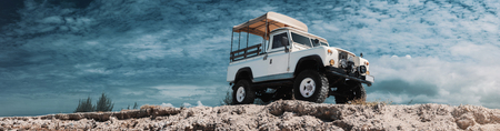 Panoramic photo of safari car on offroad , adventure trail. On high, Bottom view, sky and clouds on background, With empty space for logo or text