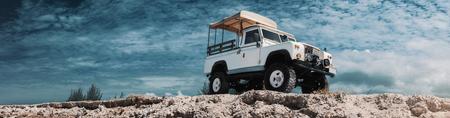 Panoramisches Foto des Safariautos auf nicht für den Straßenverkehr, Abenteuerspur. Hoch, Ansicht von unten, Himmel und Wolken im Hintergrund, mit leeren Platz für Logo oder Text