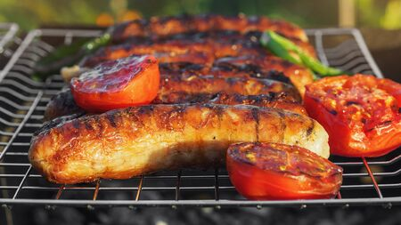 Grilling sausages on barbecue grill with vegetables. Selective focus. Stock Photo