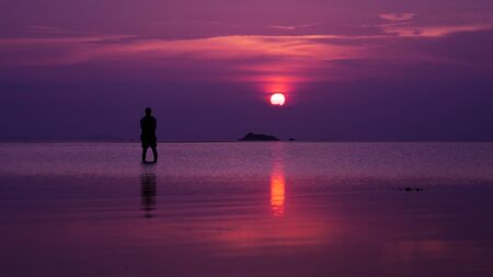 silhouette of man standing in sea at sunset Stock Photo