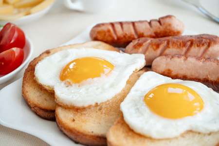 Breakfast with love - fried eggs in the shape of a heart, fried sausages and coffee