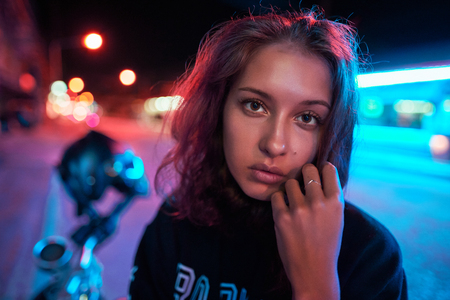 Neon close up portrait of young woman wear hoodie. night city street shot