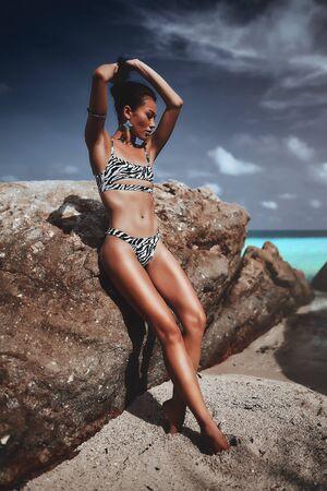 sexy girl in zebra colored bikini posing on blue sea background