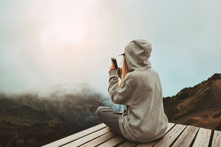a girl in a grey hoodie sitting on a viewpoint and take a picture on smart phone