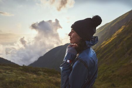 A young woman hiker in a blue jacket standing in the mountains