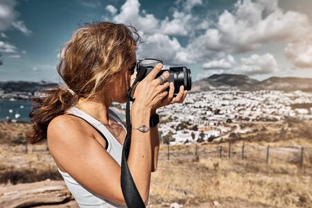 Beautiful woman professional photographer with dslr camera shooting landscape in sunset light in Turkey