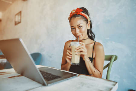 a young asian woman using laptop in cafe
