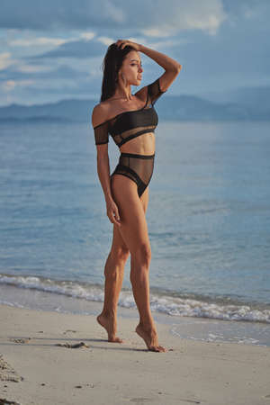 beautiful sexy woman in black swimwear posing at the beach and looking in camera