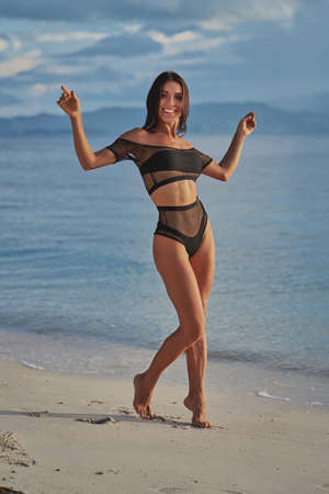 beautiful sexy woman in black swimwear posing at the beach and looking at camera