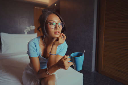 Beautiful asian woman holding and drinking coffee on the bed in the morning