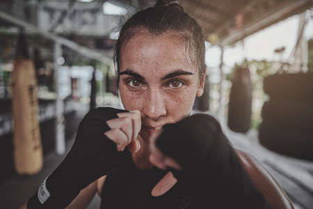 Portrait of a woman standing in striking pose and looking at camera at dark ring. Portrait of woman kickboxer ready to punch