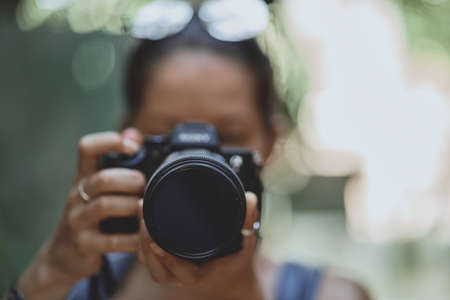 Lifestyle portrait of a Woman photographer taking photo by digital camera. Selective focus at lens Banque d'images