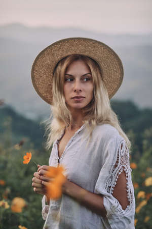 The blonde in a linen dress walks among herbs and wildflowers on a meadow in the mountains