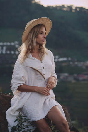 The blonde in a linen dress and straw hat sits on a viewpoint in the mountains Imagens