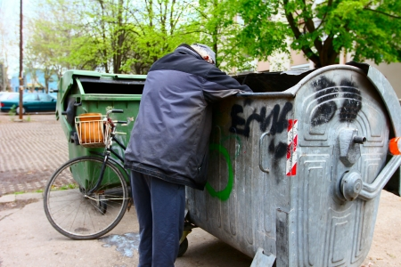 A homeless man looking for food in a garbage dumpster  photo