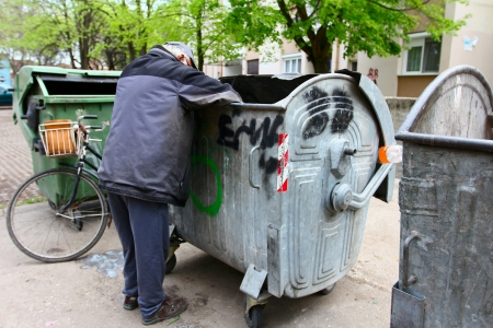A homeless man looking for food in a garbage dumpster