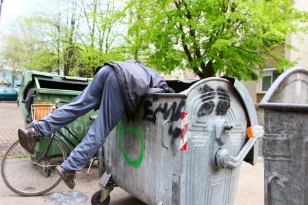 A homeless man looking for food in a garbage dumpster Imagens - 18258973