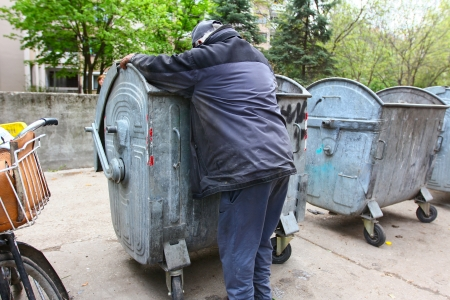 A homeless man looking for food in a garbage dumpster Stock Photo - 18258976