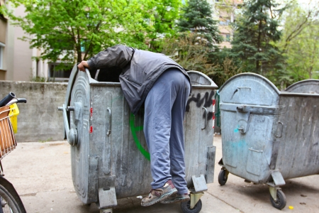 18258927-a-homeless-man-looking-for-food-in-a-garbage-dumpster.jpg