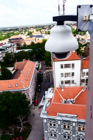 High tech overhead security camera at a tall building oversees City area  photo