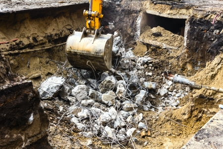 trenching: Excavator digging up the remains of a broken reinforced concrete