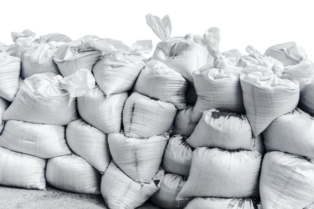 overflows: White sandbag bags are full with sand in wall formation and ready for defense