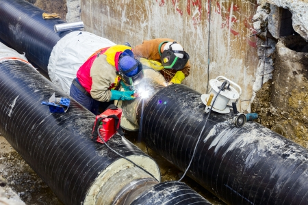 Welders with protective equipment welding outdoors pipeline construction.