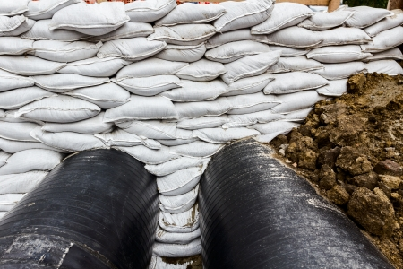 industrially: White sandbag bags are full with sand in wall formation to hold the Earth near traffic road  Industrially isolated pipes for distance heating passes under the road