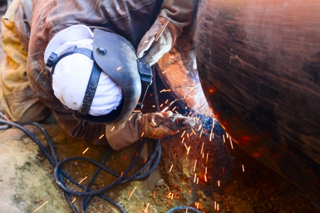 safety equipment: Welder working on a pipeline in construction site wearing overall and safety equipment