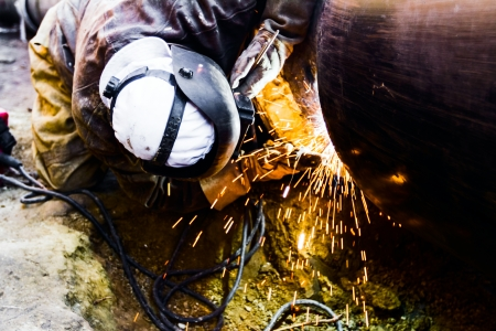 Welder working on a pipeline in construction site wearing overall and safety equipment