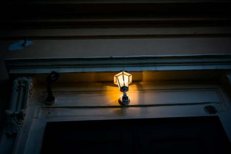 Front door with security camera and illuminated porch light