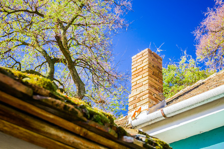 Mossy roof and brick smoke stack on blue sky photo