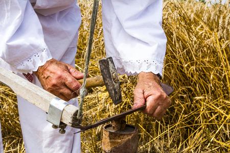 男は穀物を刈るに使用される鎌をシャープします。