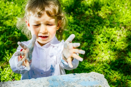Child with dirty hands looking in too concrete trash can
