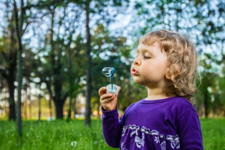 Beautiful little girl blowing soap bubbles in park. photo