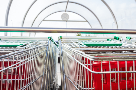 Many carts arranged in line at big supermarket  Stacked shopping carts  photo