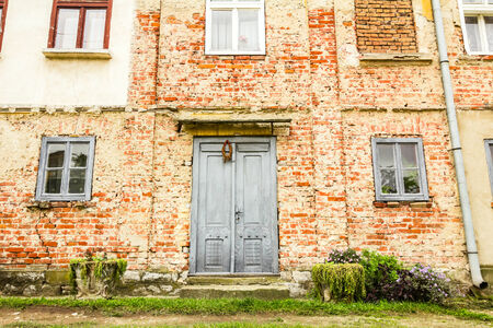 doorstep: Old house brick wall with painted door and window