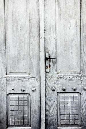 view of a wooden doorway: Old gray decorated door in close-up view