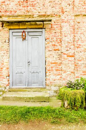 doorstep: Old gray door, decorated with dried wreath.