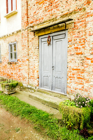 Old house brick wall with painted door and window photo