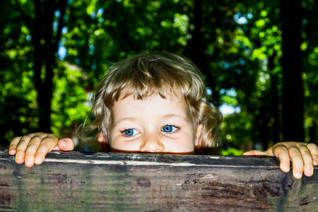 Little 3 year old girl peek over the wooden bars. photo