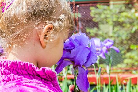 アイリスの花と遊ぶことを楽しんでいる若い女の子
