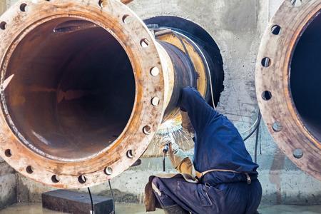 trabajador petroleros: Trabajador la soldadura de dos tubos grandes en a la salida de la zanja Foto de archivo