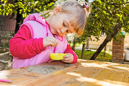 Cute girl enjoy playing cooking in garden on wooden table photo