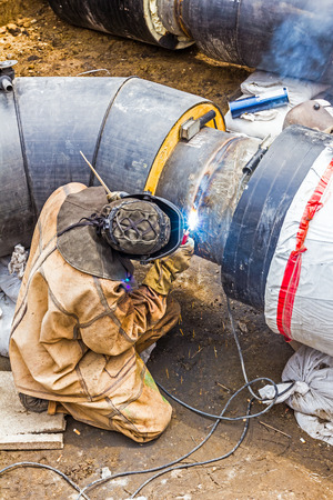 specific clothing: Welder welding a pipe on a terrain Stock Photo
