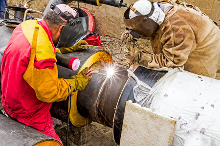 Welders welding pipeline together, teamwork photo