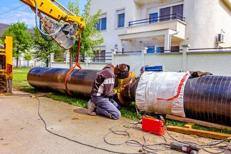 Work is in progress, welding pipeline in urban area. photo