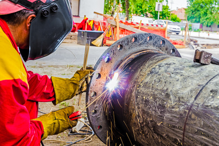Welder is welding a pipe in a trench. Stock Photo