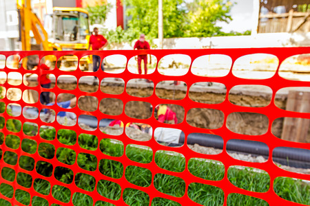mesh fence: Pipeline under construction that is blocked off with a orange fence for safety.