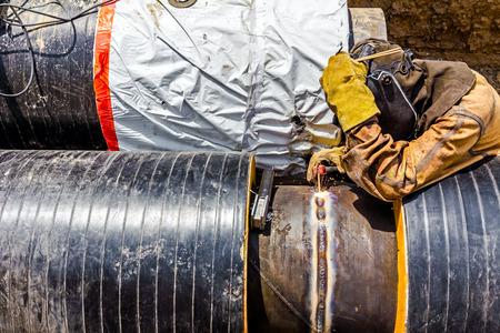 specific clothing: Welder is welding a pipe in a trench. Stock Photo